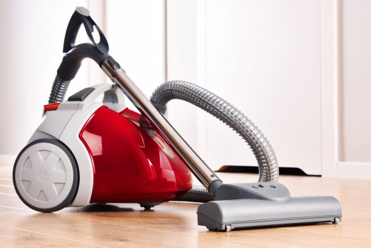 Canister vacuum cleaner for home use on the floor.