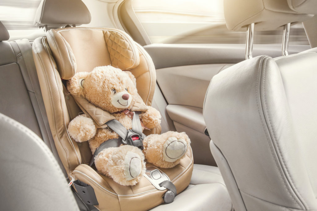 Baby child seat car. A beige teddy bear is fastened with seat belts in a car seat. Travel by car.